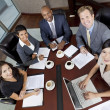 Interracial Men & Women Business Team Meeting in Boardroom - Stock Photo