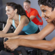African American Woman Spinning Exercise Bike at Gym - Stock Photo