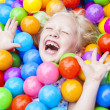 Stock Photo: Blond Girl Child Having Fun Playing in Colored Balls