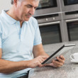 Man Using Tablet Computer in Kitchen Drinking Coffee — Stock Photo #21718899