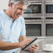Man Using Tablet Computer in Kitchen Drinking Coffee — Stock Photo #21718939