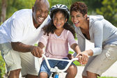 African American Family WIth Girl Riding Bike & Happy Parents — Stock Photo