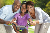 African American Family WIth Girl Riding Bike & Happy Parents — Stockfoto
