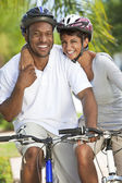 Happy African Man & Woman Couple Riding Bike Smiling — Stock Photo