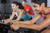 African American Woman Spinning Exercise Bike at Gym — Stock Photo