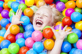 Blond Girl Child Having Fun Playing in Colored Balls — Stock Photo