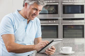 Man Using Tablet Computer in Kitchen Drinking Coffee — Stock Photo