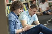 étudiants garçon mâle à l'aide de tablettes électroniques en bibliothèque — Photo