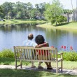 Senior African American Couple Sitting On Park Bench - Foto de Stock