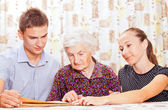 Elderly woman with the two young smileing grandchild — Stock Photo