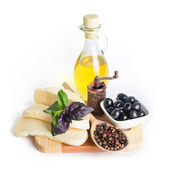 Black olives in white bowl, olive oil and cheese — Stock Photo