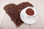 Heart of coffee beans with a cup — Zdjęcie stockowe