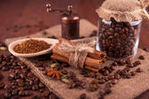 Coffee beans and cinnamon sticks on a wooden board — Stock Photo