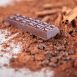 Stock Photo: Cocopowder, chocolate bars and nuts on wooden board