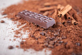 Cocoa powder, chocolate bars and nuts on a wooden board — Stock Photo