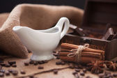 White gravy boat with cinnamon sticks and chocolate — Stock Photo