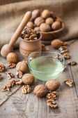 Walnuts oil and nuts in wooden bowls on wooden table — Stock Photo
