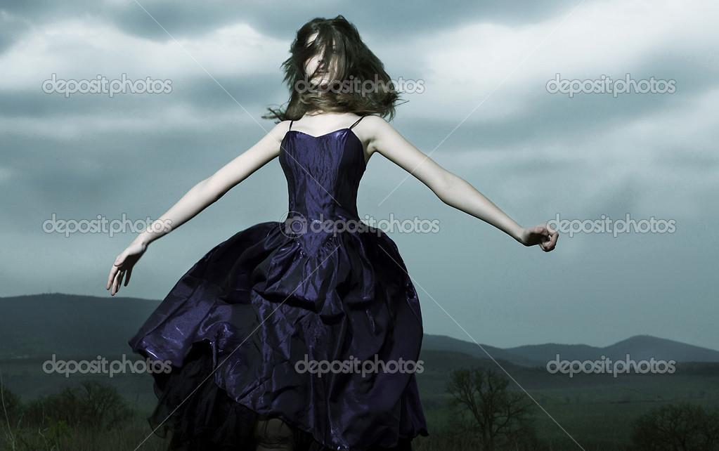 天空的背景上穿裙子的女孩