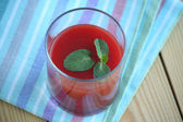 Tomato juice in glass and fresh mint leaves on wooden background — Stockfoto