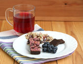 Muesli snack bar, blueberries and berry tea — Stock Photo