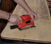 Sanding wooden table — Stock Photo