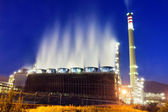 Industrial refinery at night with cooling water smoke — Stock Photo