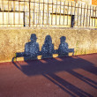 Stock Photo: Shadow of people resting on a bench