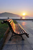 Bench on promenade at sunset — Stock Photo