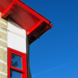 House facade with red roof and window against blue sky — Stock Photo