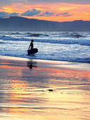 Surfer with boogie board at sunset — Stock Photo