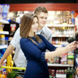 Foto Stock: Young couple shopping at supermarket