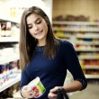Woman choosing yogurt in supermarket — Stock Photo
