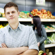 Young man standing the front of shopping shelves — Stock Photo