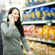 Royalty-Free Stock Photo: Beautiful woman on mobile phone at supermarket