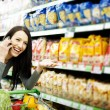 Beautiful woman on mobile phone at supermarket — Stock Photo