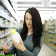 Woman choosing bottle of milk at supermarket — Stock Photo