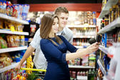 Young couple shopping at supermarket — Stok fotoğraf