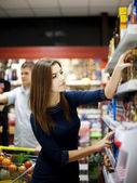 Young woman trying make a choice in supermarket — Stock Photo