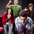 Friends bowling together - Stock Photo