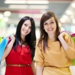 Two girlfriends with shopping bag - Stok fotoğraf