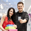Happy young couple spending money at clothing store — Stock Photo #21825891