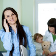 Busy businesswoman taking her daughter to the doctor — Stock Photo