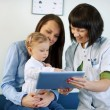Doctor showing mother's medical results on the tablet — Stock Photo