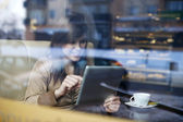 Young woman using tablet in coffee shop — Stock Photo