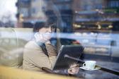 Mujer joven usando tableta en cafetería — Foto de Stock