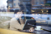 Young woman using tablet in coffee shop — Foto de Stock