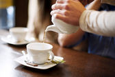 Waitress pouring cup of coffee or tea — Stock Photo