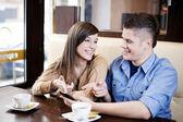 Par lyssnar musik i café — Stockfoto