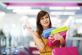 Beautiful woman with credit card in shopping mall — Stock Photo