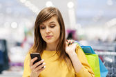 Young woman texting on mobile phone in store — Stock Photo